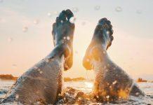 muzske nohy v mori pri zapade slnka