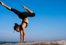 mlada zena cvici jogu na skale