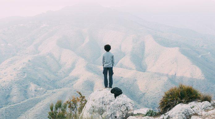 muz medituje na okraji skaly