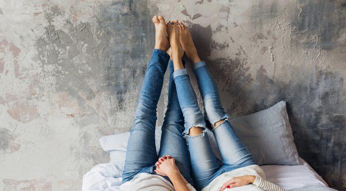 muzske a zenske nohy v denime oprete o stenu