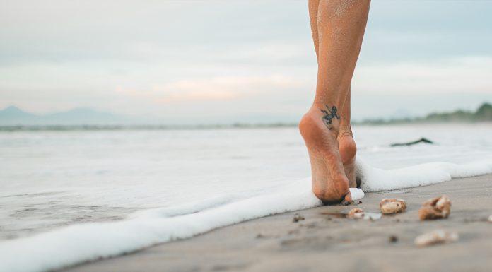 nohy zeny ktora sa prechadza po plazi